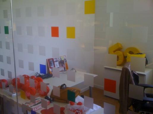 El clásico vidrio con recuadros de colores que separa las oficinas del personal jerárquico.