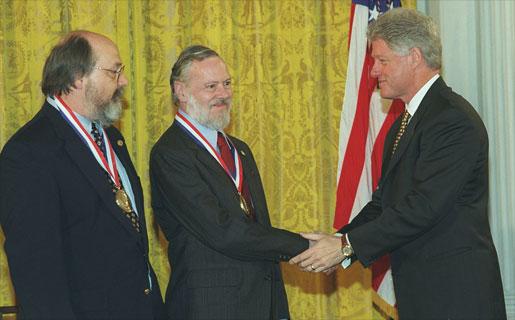 Ken Thompson (izq) y Dennis Ritchie (centro) recibiendo la Medalla Nacional de Tecnología en 1998 de manos del entonces presidente Bill Clinton (der). Fuente: Wikipedia