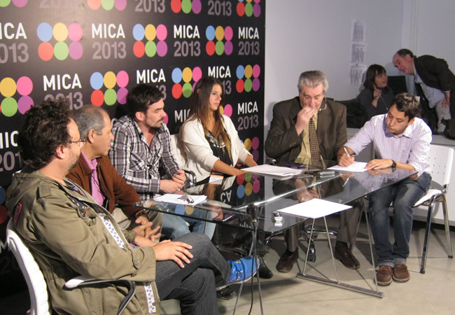 Matìas Botbol, de Taringa, firmando el acuerdo. A su izquierda, Isaac Rubinzal, presidente de la CAL.
