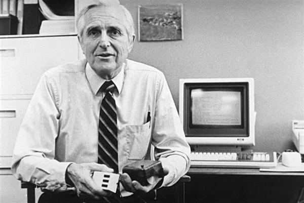 Engelbart, junto a su más famosa creación, el mouse.
