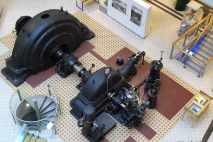 Una turbina con su correspondiente generador de energía exhibido en una de las plantas. Incluso se puede apreciar la parte inferior bajando por una escalera.