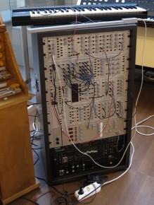 Un rack con módulos de generación y procesamiento de sonidos interconectados y ejecutados por el pequeño teclado situado arriba.