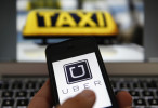 An illustration picture shows the logo of car-sharing service app Uber on a móvil next to the picture of an official German taxi sign